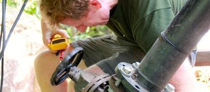 EM member working on a pipe