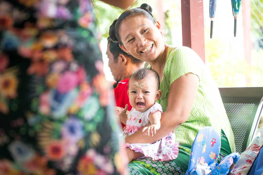 A mother smiling holding her crying child in her arms at the T-RAD Clinic.