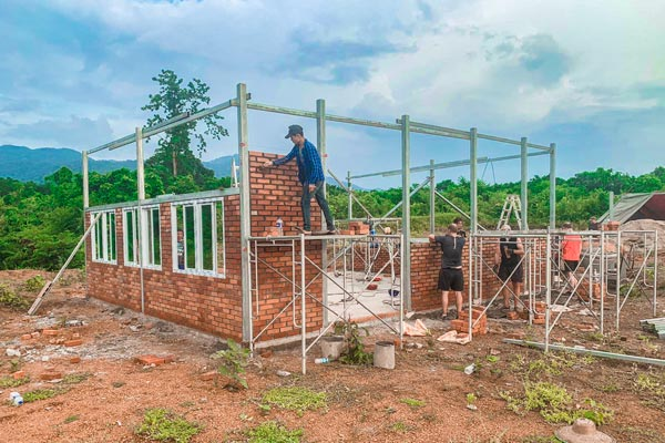 An Engineering Technology graduate (center) building a classroom with a group of engineering volunteers from Ireland